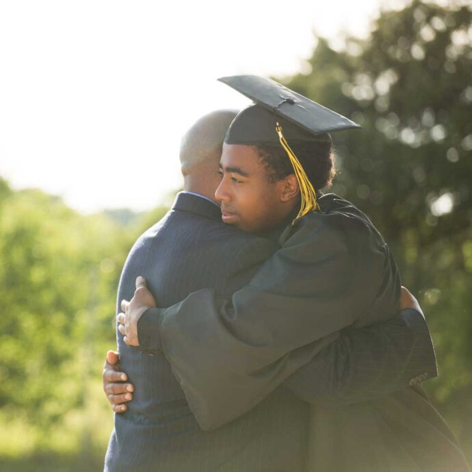 African American adolescent in graduation gown hugging family member